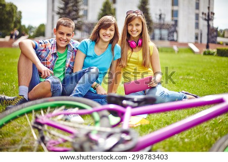 Cheerful teenage friends relaxing on green lawn in summer - stock photo