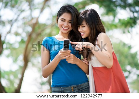 Cheerful teenage girls texting and laughing outdoors - stock photo