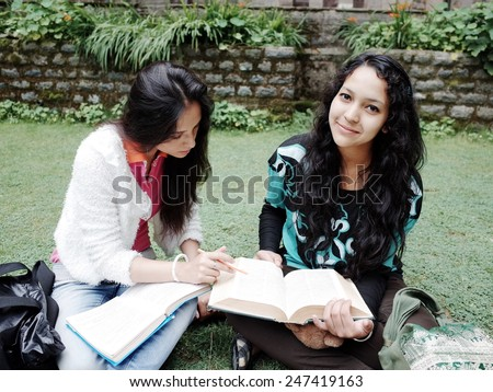 Cheerful teenager friends studying together over grass. - stock photo