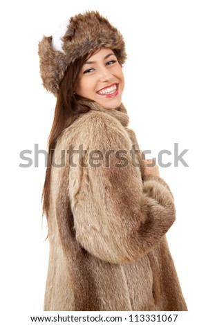 cheerful teenager girl in fur coat and hat, white background - stock photo