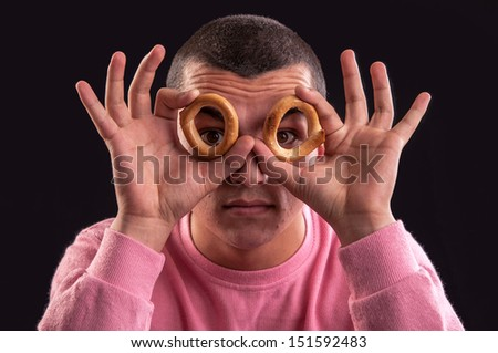 cheerful teenager look through a bagels hole - stock photo