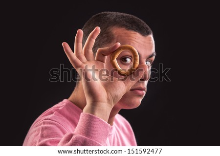 cheerful teenager look through a bagels hole, focus on bagel - stock photo