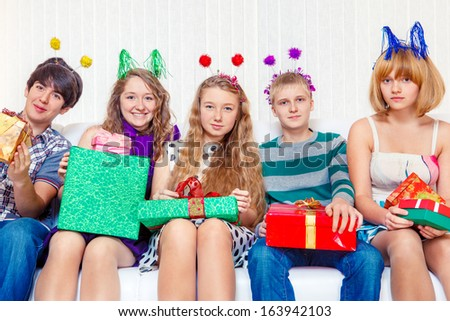 Cheerful teenagers hold party presents - stock photo