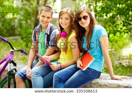 Cheerful teens spending time together after school - stock photo