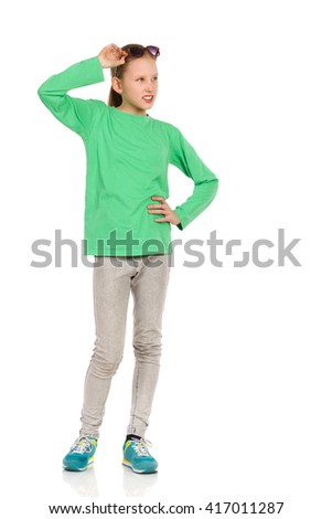 Cheerful ten years old girl in green blouse, jeans and holding hand on hip and looking away. Full length studio shot isolated on white. - stock photo