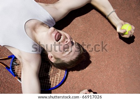 Cheerful Tennis Player Holds A Ball While Laying On His Back In A Winning Expression - stock photo