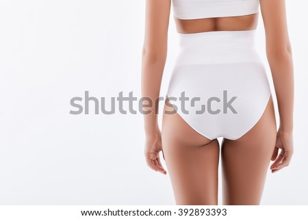 Cheerful thin girl is showing her back - stock photo