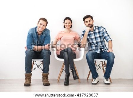 Cheerful three colleagues have sit with anticipation - stock photo