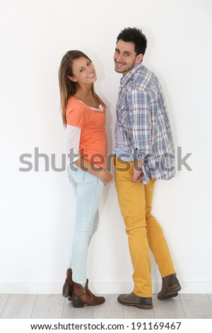 Cheerful trendy couple on white background - stock photo