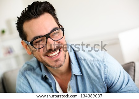 Cheerful trendy guy with black eyeglasses on - stock photo