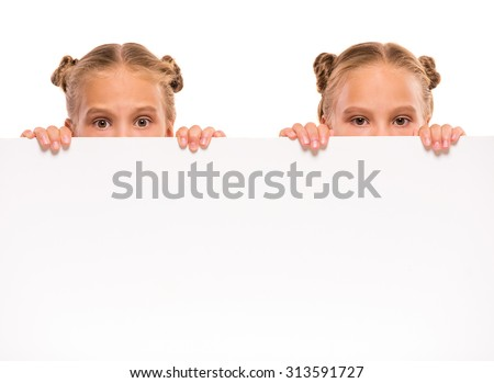 Cheerful twins girls with a white board isolated in white background. - stock photo