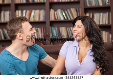 Cheerful two friends are showing tongue to each other. They are drawing faces and laughing. The man and woman are sitting on sofa in the library - stock photo