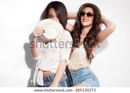 cheerful two young women in summer clothes have fun wearing jeans shorts sunglasses and hats  - stock photo