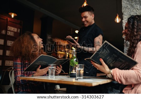 Cheerful two young women sitting at cafe holding menu card giving order to waiter. Young woman placing order to a waiter at restaurant while sitting with her friend. - stock photo