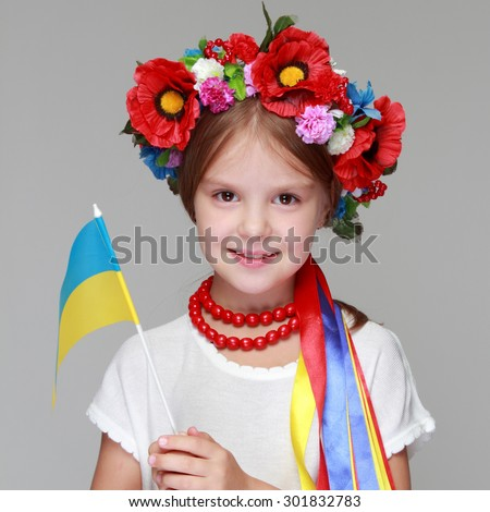 Cheerful Ukrainian smiling little girl with a wreath on head - stock photo