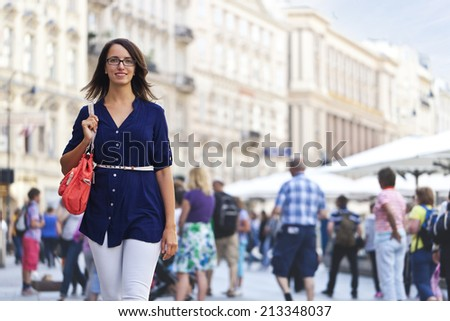 Cheerful urban girl standing out from the crowd at a city street - stock photo