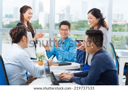 Cheerful Vietnamese business team applauding - stock photo