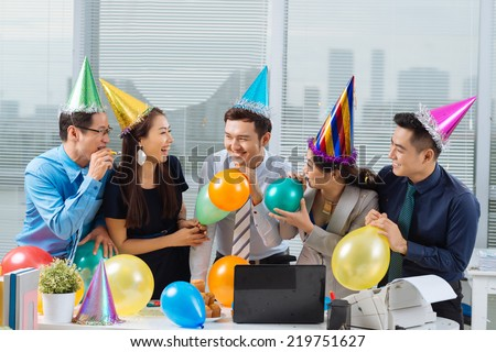 Cheerful Vietnamese business team having party in the office - stock photo
