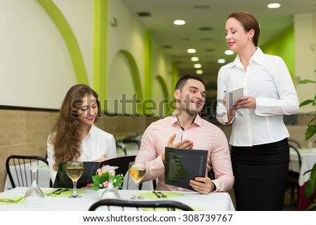 Cheerful waitress offering to young couple of tasty dishes - stock photo