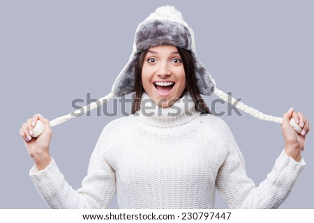 Cheerful winter girl. Happy young women in warm winter clothing having fun while standing against grey background - stock photo