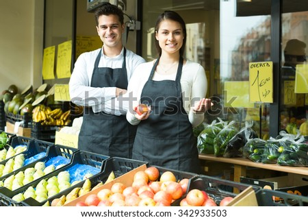 Cheerful woman and man selling fresh vegetables and fruits on market - stock photo