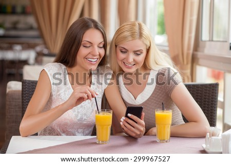 Cheerful woman are sitting at the table in cafe. They are drinking juice. One lady is holding a mobile phone. The friends are looking at it with interest and smiling - stock photo