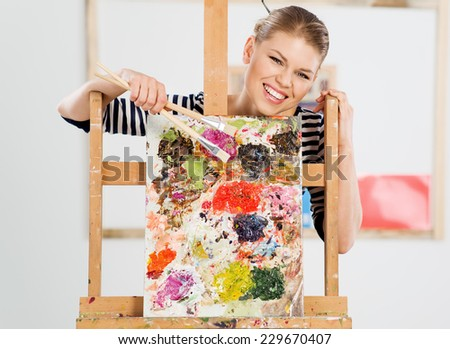 Cheerful woman artist with paintbrushes and color palette posing in artistic studio. Happy smiling Caucasian girl drawing with acrylic paints.   - stock photo
