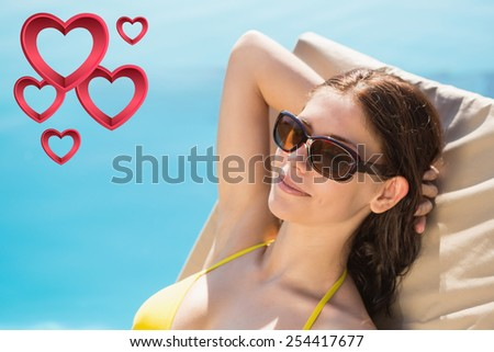 Cheerful woman by swimming pool against pink hearts - stock photo
