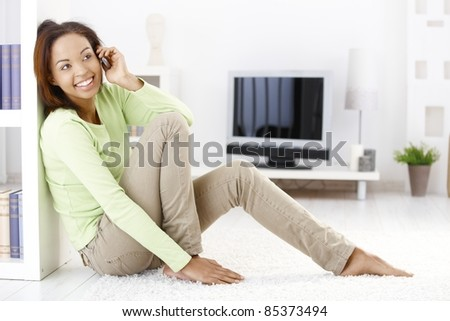 Cheerful woman calling on mobile phone, sitting in living room on floor, smiling.? - stock photo