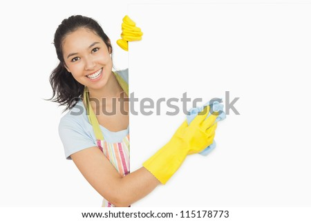 Cheerful woman cleaning white surface in apron and rubber gloves - stock photo