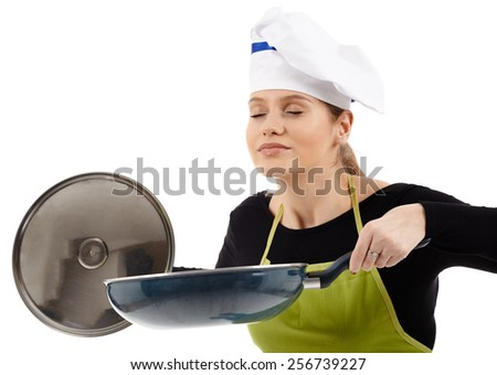 Cheerful woman cook holding a wok pan and smelling the flavor of the food - stock photo