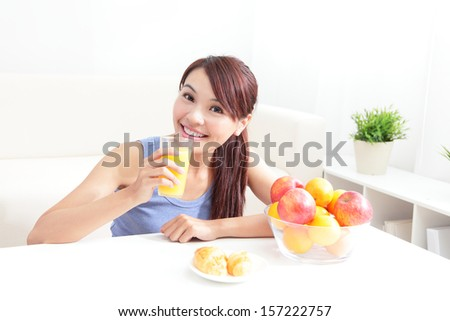 Cheerful woman drinking an orange juice sitting on her sofa at home, asian beauty - stock photo