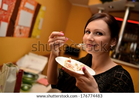 Cheerful woman eating pie - stock photo