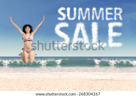 Cheerful woman enjoy holiday at beach while jumping next to summer sale cloud - stock photo