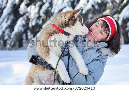 Cheerful woman having fun with her little cute Siberian Husky puppy in winter forest full of snow. Lifestyle concept - stock photo