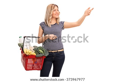Cheerful woman holding a shopping basket with groceries and reaching for something isolated on white background - stock photo