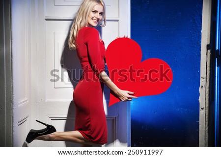 Cheerful woman holding heart symbol - stock photo