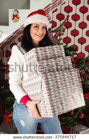 Cheerful woman holding many Christmas gifts in front of natural tree - stock photo