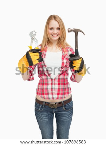 Cheerful woman holding tools against white background - stock photo