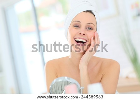 Cheerful woman in bathroom with towel over hair - stock photo