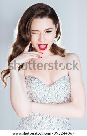 Cheerful woman in fashion dress winking isolated on a white background - stock photo