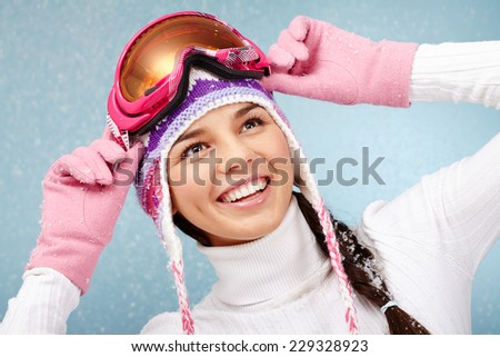Cheerful woman in goggles and knitted winter cap captured by snowfall - stock photo