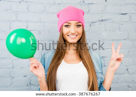 Cheerful woman in pink hat holding green balloon and gesturing with two fingers - stock photo