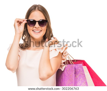 Cheerful woman in sunglasses holding colored shopping bags on white background. - stock photo
