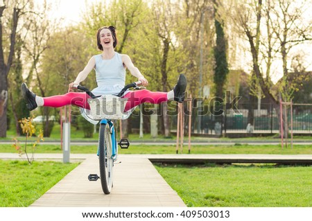 Cheerful woman in the park smiling and riding bicycle with her legs in the air and having fun - stock photo