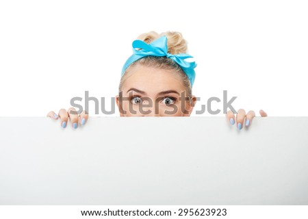 Cheerful woman is hiding behind white wall. She is scared. Isolated on background - stock photo