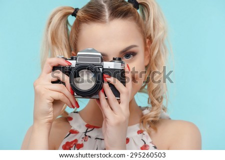 Cheerful woman is photographing with camera. She is looking forward with interest. The lady is smiling gently. Isolated on blue background - stock photo