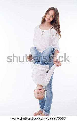 Cheerful woman is playing with her child. The boy is embracing a female waist with his hands. He is hanging down. They are holding hands and smiling. Isolated on background - stock photo