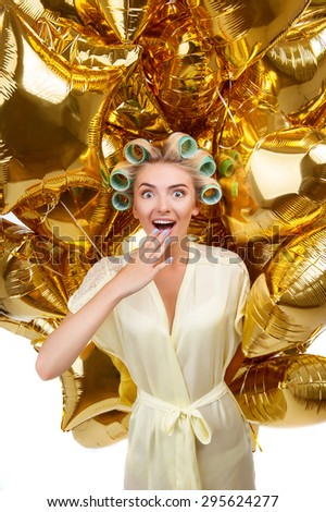 Cheerful woman is showing her surprise and happiness. She is receiving a great amount of golden balloons. The lady has curlers in her hair - stock photo