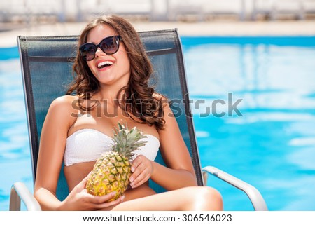 Cheerful woman is sitting in a chair near a swimming pool. She is holding a pineapple and laughing. The lady is sunbathing and relaxing. Copy space in right side - stock photo